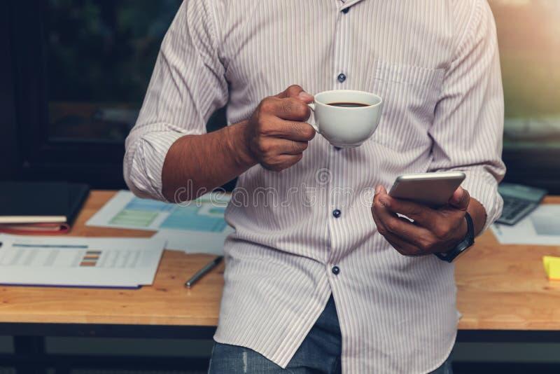 Biznesu i finanse pojęcie biurowy działanie, biznesmen używa smartphone i trzymający filiżankę w biurze obraz stock