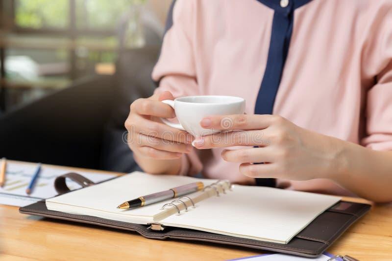 Biznesu i finanse pojęcie, bizneswoman trzyma filiżankę i dyskutuje sprzedaży analizy mapę w sklep z kawą obraz stock