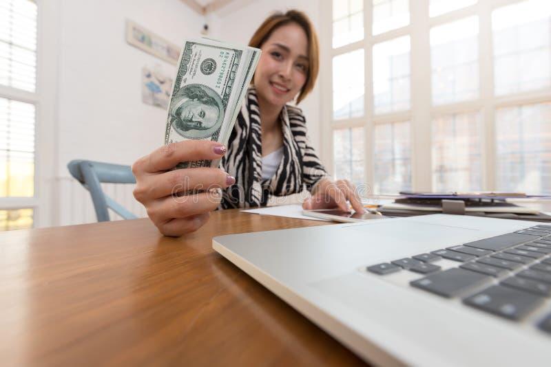 Biznesu i finanse pojęcie, bizneswomanu mienie gotówkowy i używa laptop dla handlu elektronicznego online zakupy obraz royalty free