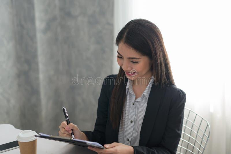 bizneswomanów azjatykci piękni potomstwa Szczęśliwy działanie w jej workst fotografia stock