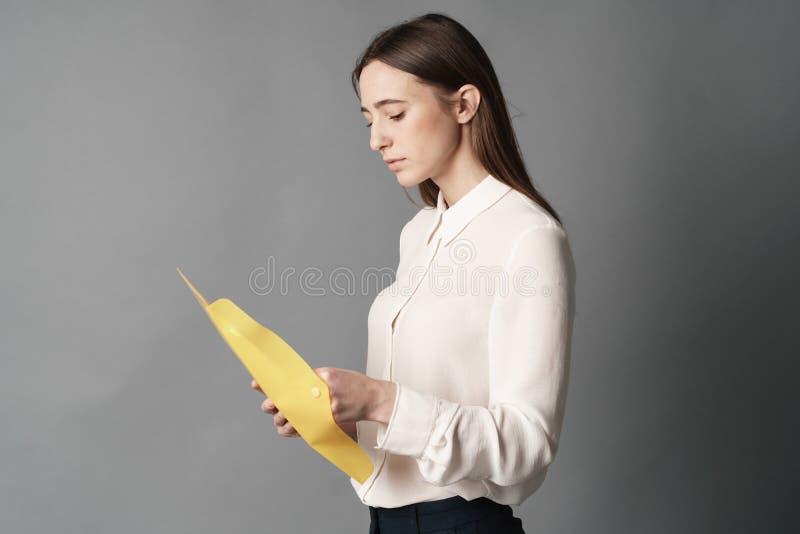 Bizneswomanów chwytów dokumenty w ona ręka jeden Odizolowywający na szarym tle obraz stock