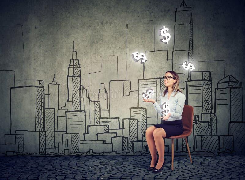 Bizneswoman żongluje z dolarowymi symbolami na pejzażu miejskiego tle zdjęcie stock