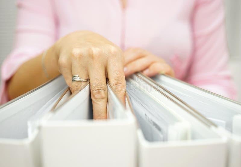 Bizneswoman bierze jeden segregatoru od inny fotografia stock