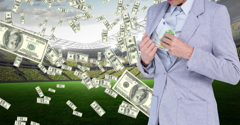 Bizneswoman chuje pieniądze w kurtce przy stadionem futbolowym reprezentuje korupcję obraz stock