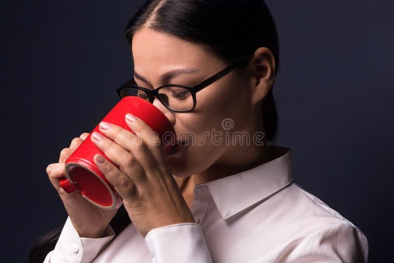 Bizneswoman cieszy się kawowej przerwy mienia czerwieni filiżankę fotografia stock