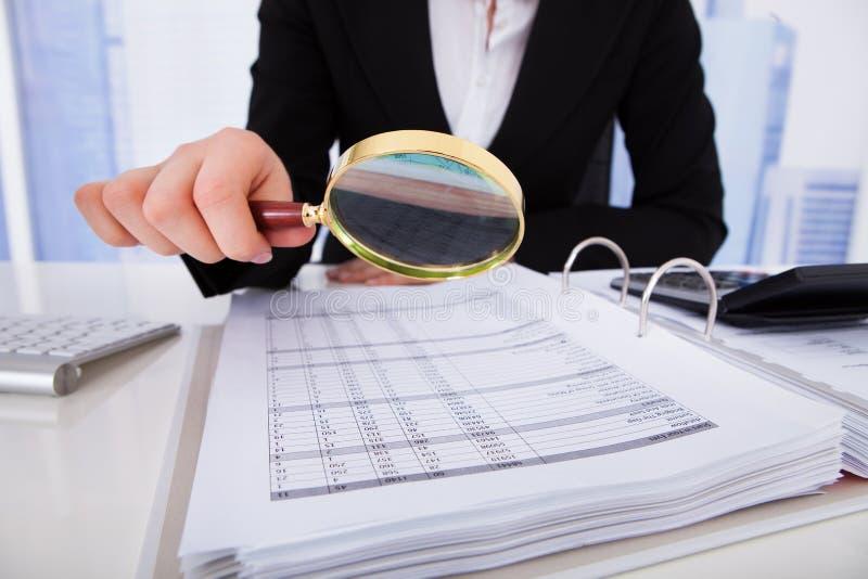 Bizneswoman dokładnie badać rachunki z powiększać - szkło zdjęcia royalty free