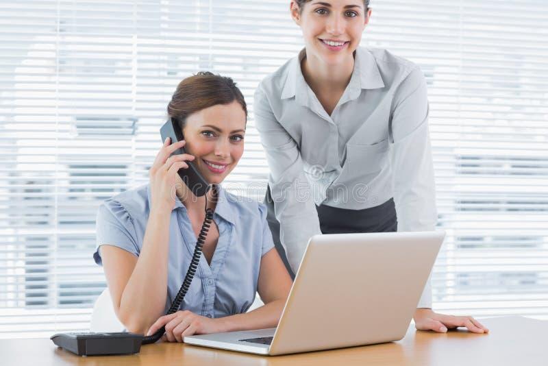 Bizneswoman dzwoni i ono uśmiecha się przy kamerą z co pracownikiem obrazy stock