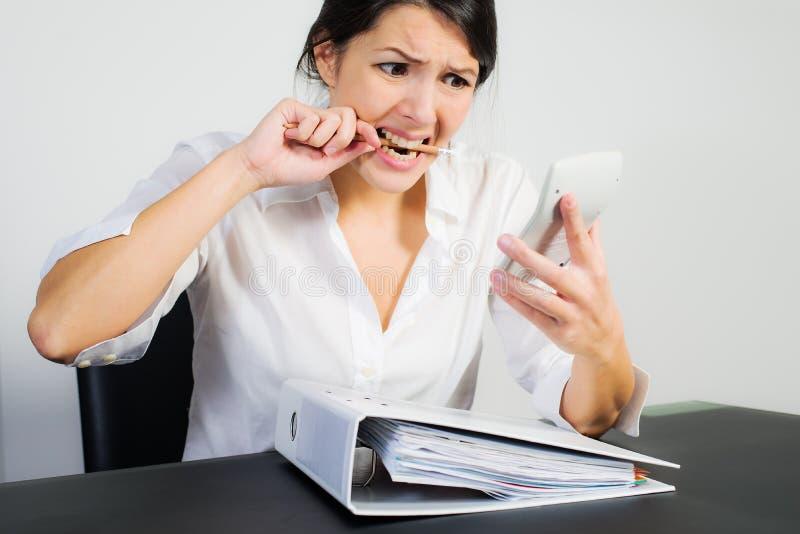 Bizneswoman gryźć jej pióro w frustraci fotografia royalty free
