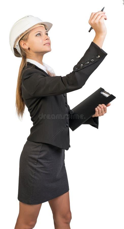 Bizneswoman jest ubranym ciężkiego kapelusz, trzyma schowek zdjęcie stock