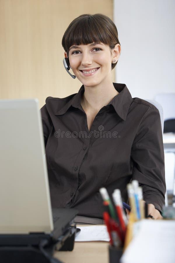 Bizneswoman Jest ubranym słuchawki obsiadanie Przy biurkiem zdjęcie royalty free