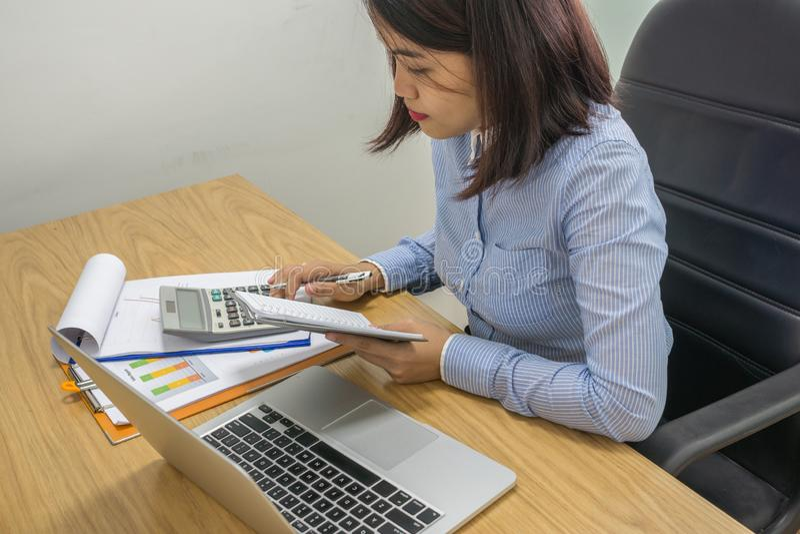 Bizneswoman kalkuluje pieniężną liczbę na kalkulatorze fotografia stock