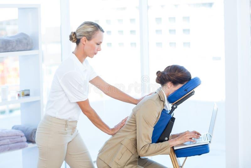 Bizneswoman ma tylnego masaż podczas gdy używać jej laptop obraz stock