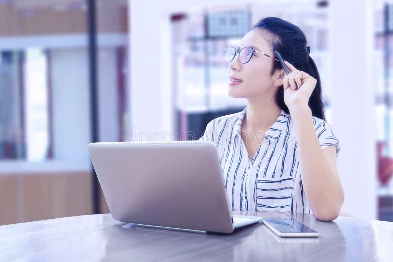 Bizneswoman myśleć pomysł podczas gdy pracujący z laptopem obrazy stock