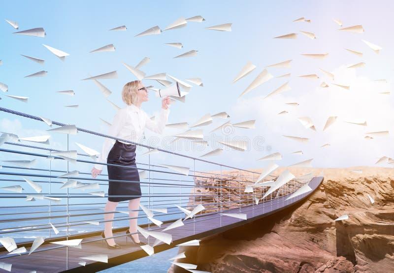 Bizneswoman na bridżowym używa megafonie fotografia stock