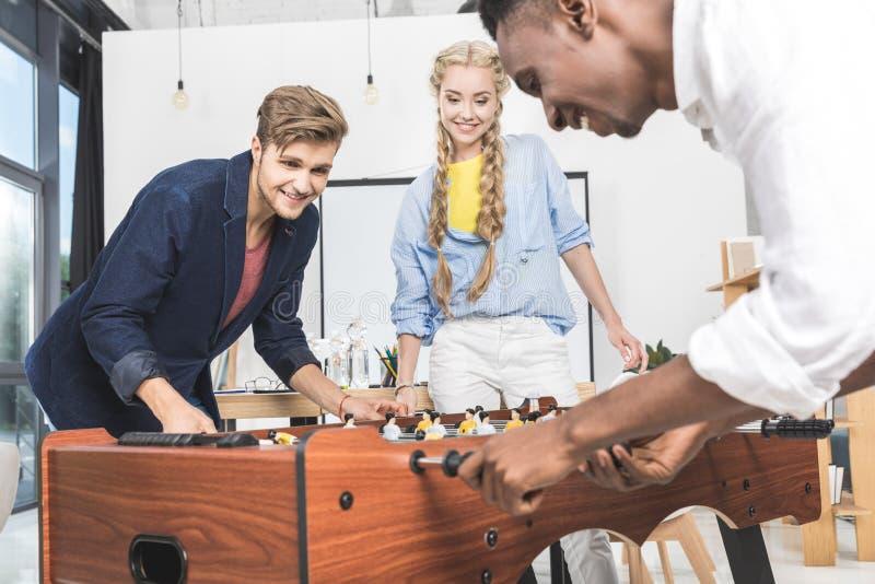 bizneswoman ogląda wielokulturowych kolegów bawić się stołowego futbol zdjęcia royalty free