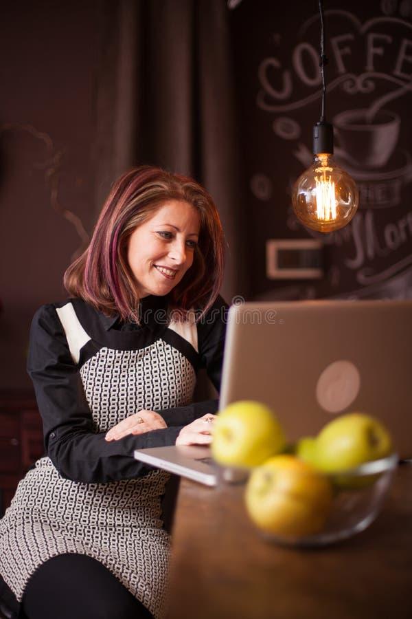 Bizneswoman ono uśmiecha się podczas gdy patrzejący jej laptop w rocznika sklepie z kawą fotografia royalty free
