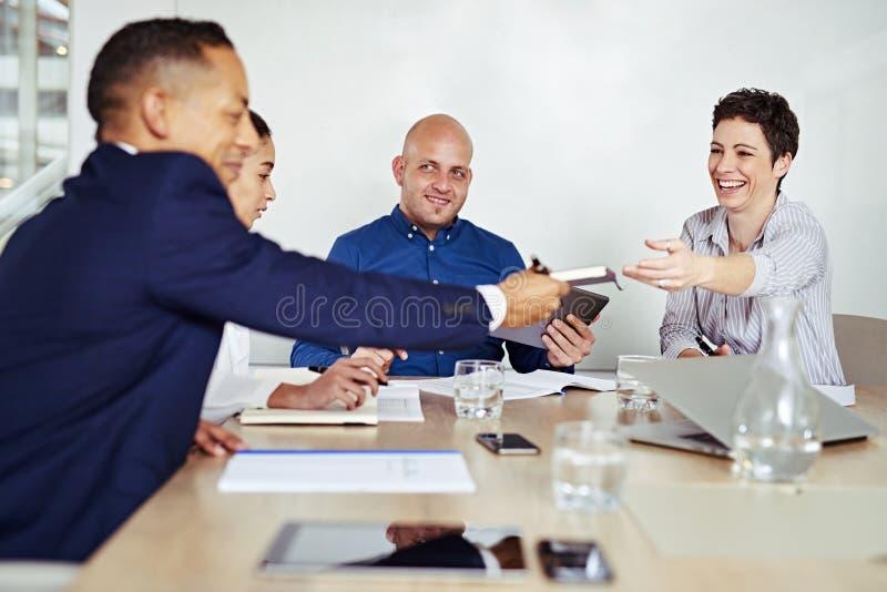 Bizneswoman ono uśmiecha się podczas gdy przechodzący notatnika biznesmen podczas spotkania obraz stock