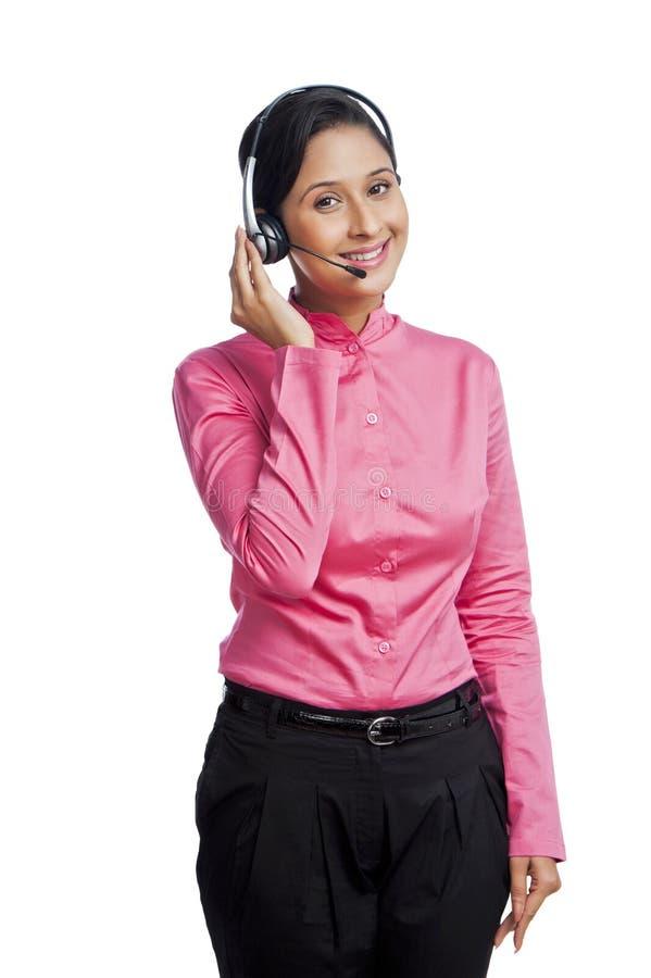 Bizneswoman opowiada na hełmofonach i ono uśmiecha się fotografia royalty free