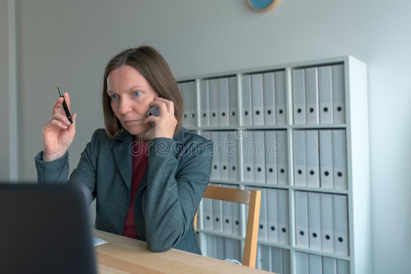 Bizneswoman opowiada na telefonie komórkowym i patrzeje laptopu ekran zdjęcia royalty free
