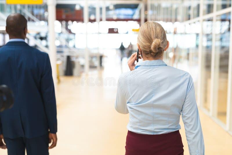Bizneswoman opowiada na telefonie komórkowym podczas gdy chodzący w korytarzu zdjęcia royalty free