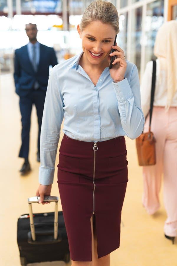 Bizneswoman opowiada na telefonie komórkowym podczas gdy chodzący z bagażem w korytarzu obrazy stock
