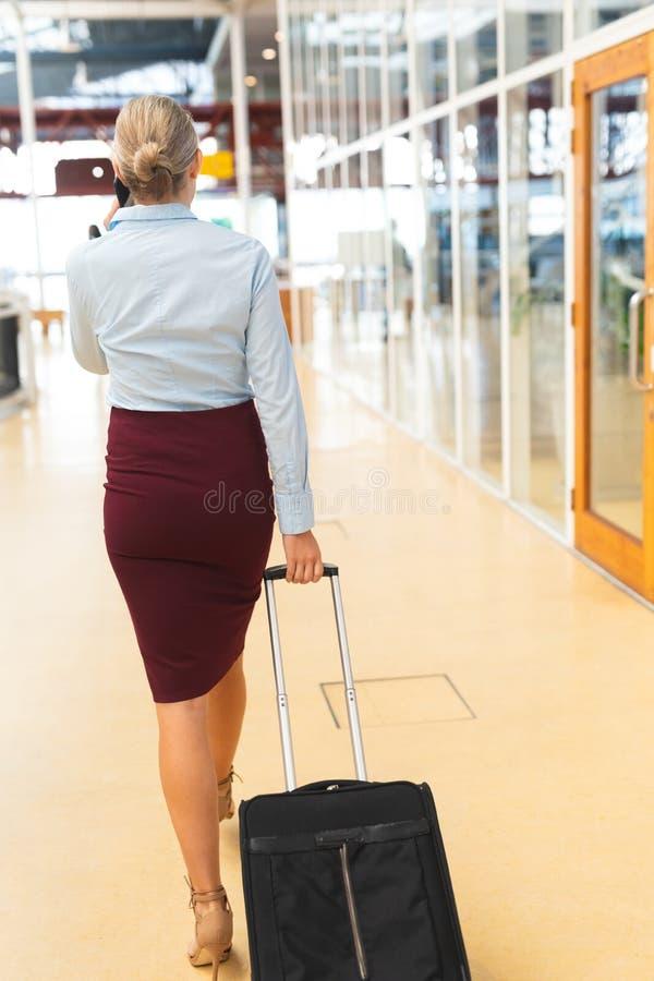 Bizneswoman opowiada na telefonie komórkowym podczas gdy chodzący z bagażem w korytarzu obraz stock