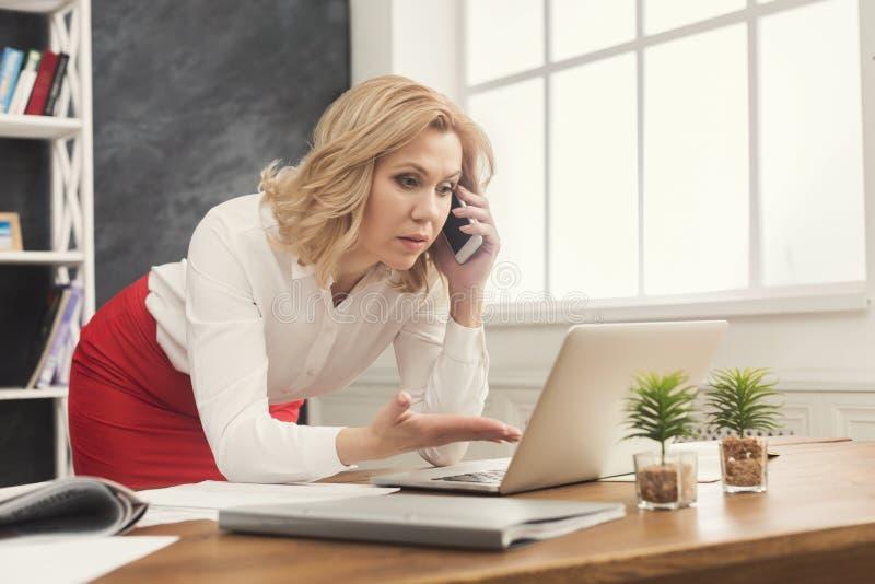 Bizneswoman opowiada na telefonie komórkowym przy biurem fotografia royalty free