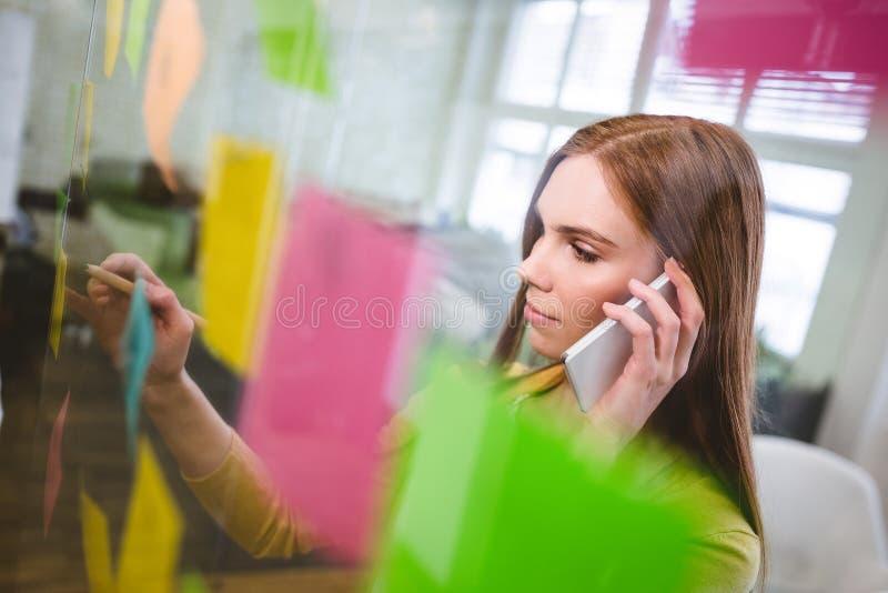 Bizneswoman opowiada na telefonu białym writing na kleistych notatkach zdjęcie royalty free