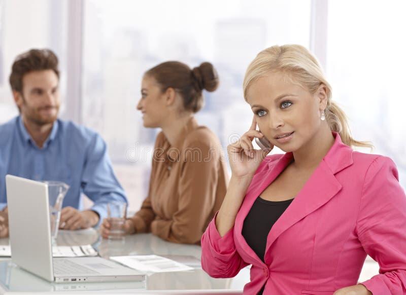 Bizneswoman opowiada na wiszącej ozdobie przy spotkaniem fotografia stock