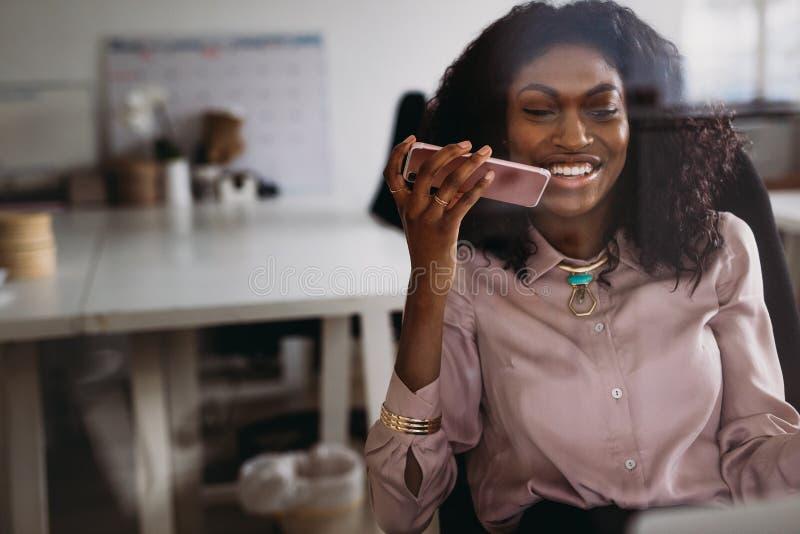 Bizneswoman opowiada nad telefonem komórkowym na głośniku podczas gdy wor fotografia stock