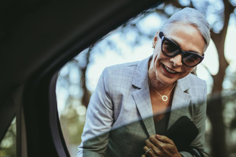 Bizneswoman opowiada z taksówkarzem obraz royalty free