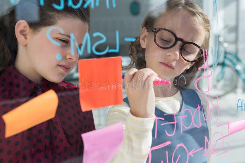 Bizneswoman patrzeje żeńskiego kolegi writing na okno obrazy royalty free