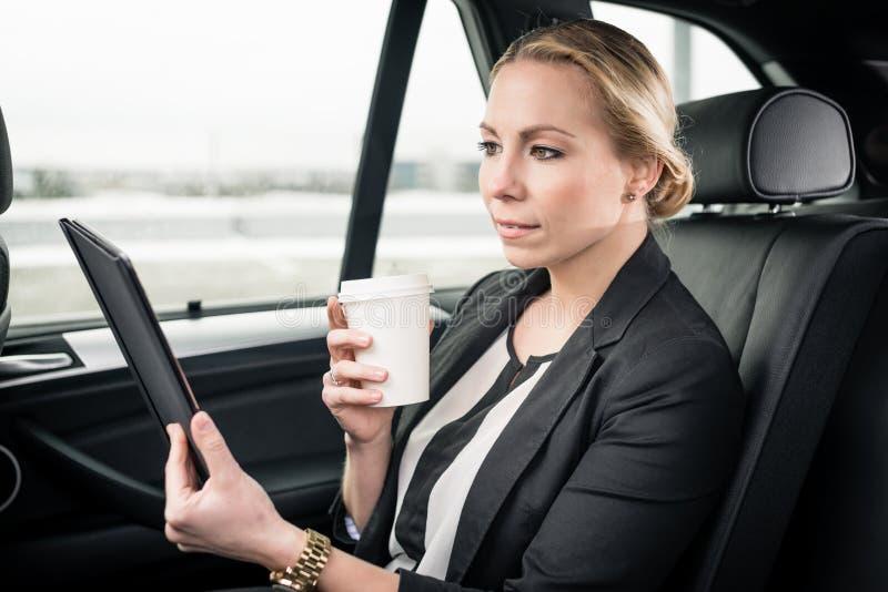 Bizneswoman patrzeje cyfrow? pastylk? w samochodzie zdjęcie royalty free