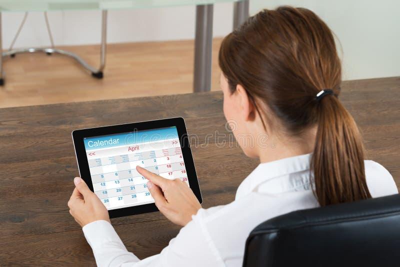 Bizneswoman Patrzeje kalendarz Na Cyfrowej pastylce obraz stock