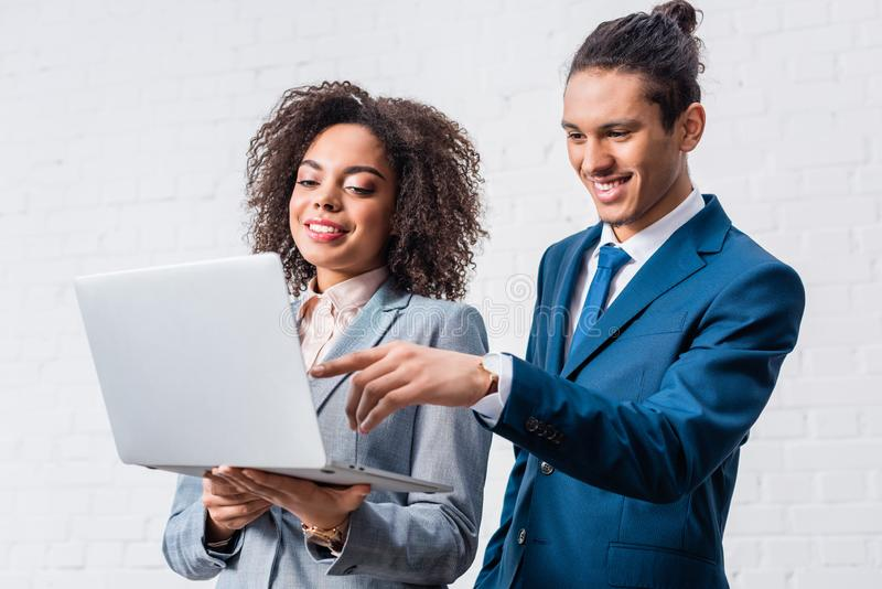 Bizneswoman patrzeje mężczyzny pracuje na laptopie na bielu fotografia stock