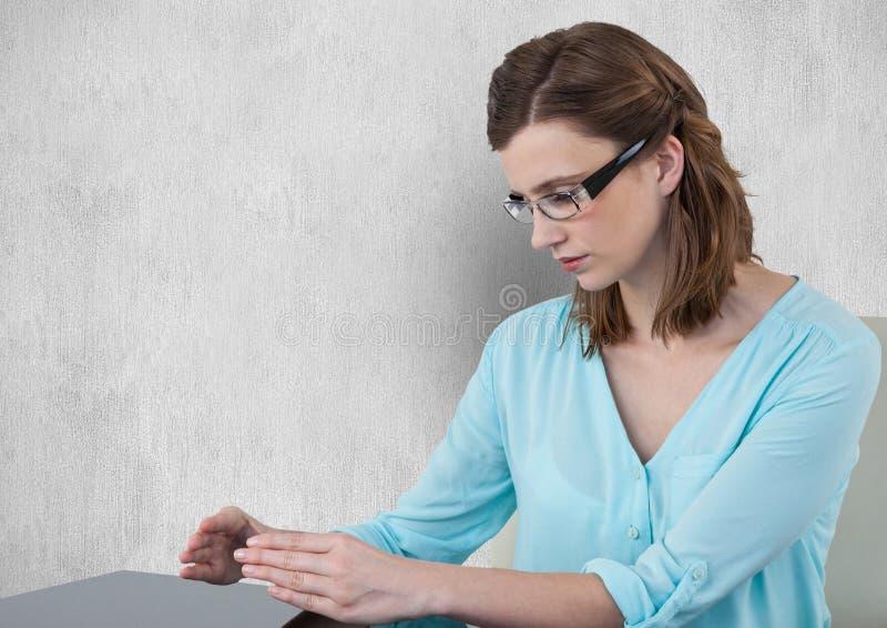 Bizneswoman patrzeje ręki przeciw szaremu tłu fotografia stock
