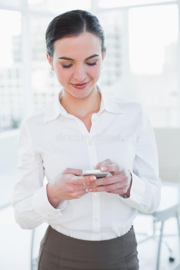 Bizneswoman patrzeje telefon komórkowego w biurze obraz stock