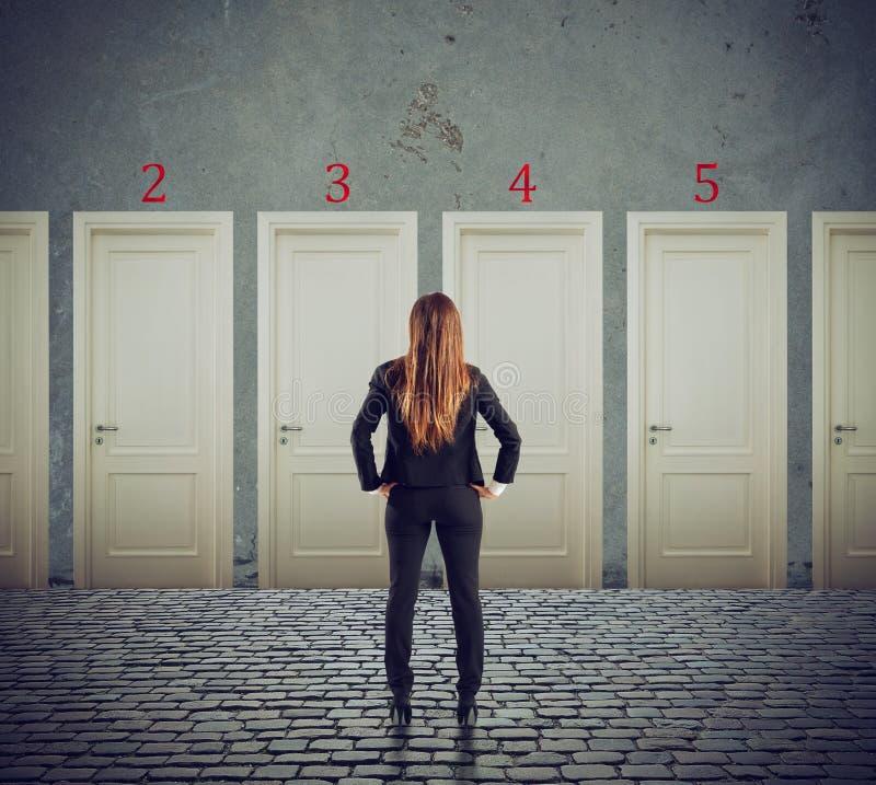 Bizneswoman patrzeje wybierać prawego drzwi Pojęcie zamieszanie i rywalizacja zdjęcie royalty free