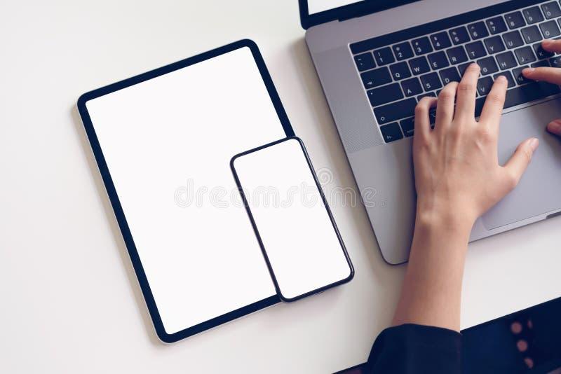 Bizneswoman pisać na maszynie klawiaturowego laptop, cyfrową pastylka i smartphone parawanowy puste miejsce na stole fotografia stock