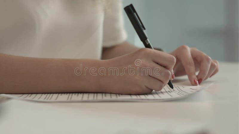 Bizneswoman pisze na dokumencie przy jej biurem obraz royalty free