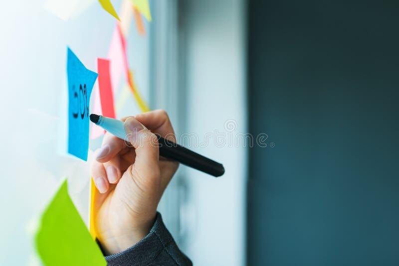 Bizneswoman pisze na kolorowym kleistym nutowym papierze obrazy stock