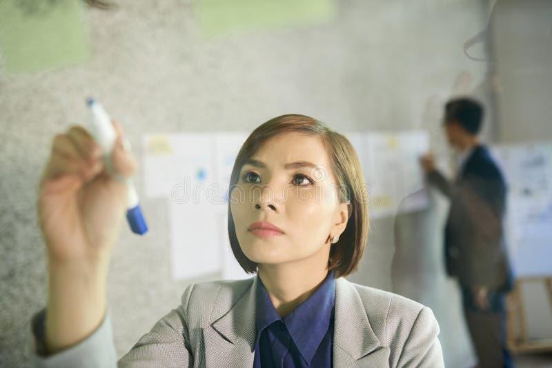 Bizneswoman pisze na szklanej ?cianie zdjęcie royalty free