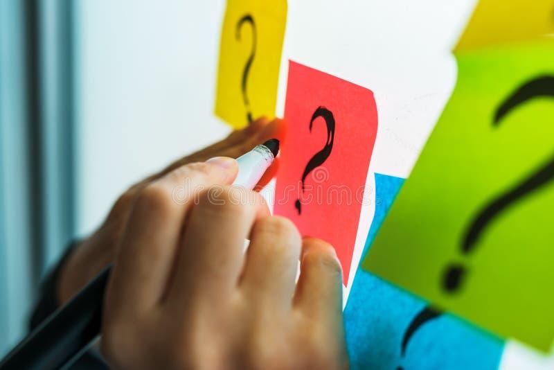 Bizneswoman pisze znak zapytania na kolorowym kleistym nutowym papierze obrazy stock