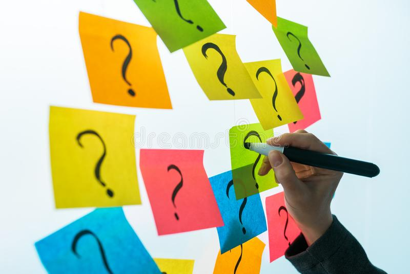 Bizneswoman pisze znak zapytania na kolorowym kleistym nutowym papierze zdjęcia royalty free