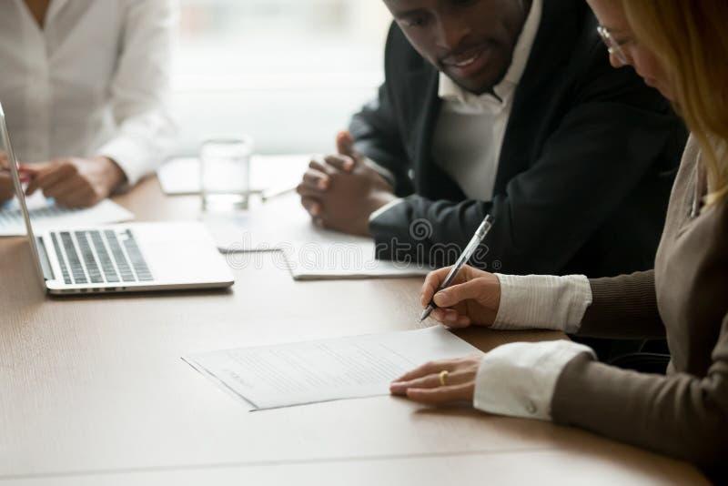 Bizneswoman podpisuje biznesowego dokument przy różnorodnym partnera spotkaniem zdjęcie stock