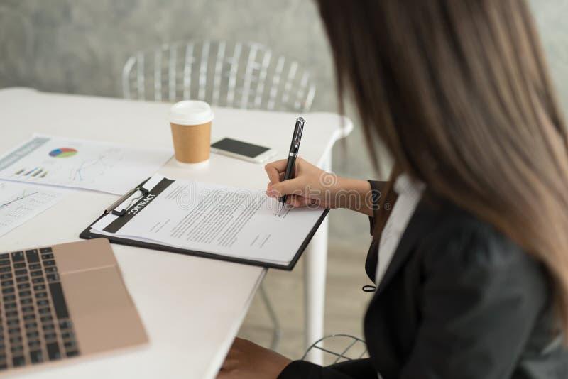 Bizneswoman podpisuje kontraktacyjnego papier w jej workstatio przy pracą fotografia stock