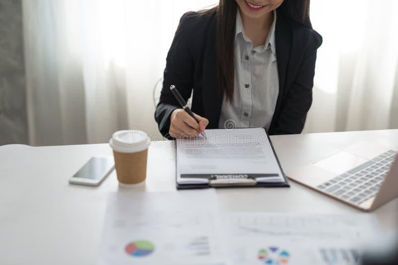 Bizneswoman podpisuje kontraktacyjnego papier w jej workstatio przy pracą obrazy royalty free
