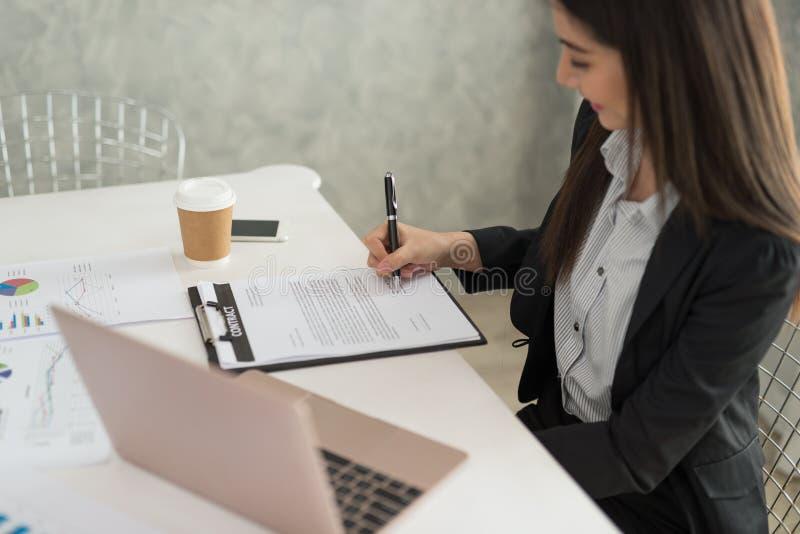 Bizneswoman podpisuje kontraktacyjnego papier w jej workstatio przy pracą obraz royalty free