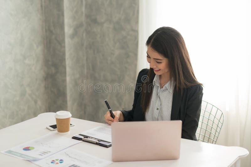 Bizneswoman podpisuje kontraktacyjnego papier w jej workstatio przy pracą zdjęcia royalty free