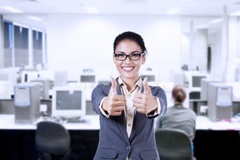 Bizneswoman pokazuje aprobaty w biurze zdjęcie royalty free